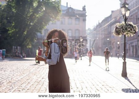 Happy attractive black woman blowwing bubbles on the street on a sunny day. Beautiful architecture around.
