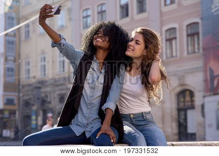 Two smiled friends making selfie. Women wearing casual clothes. One woman is black. Nice architecture background.
