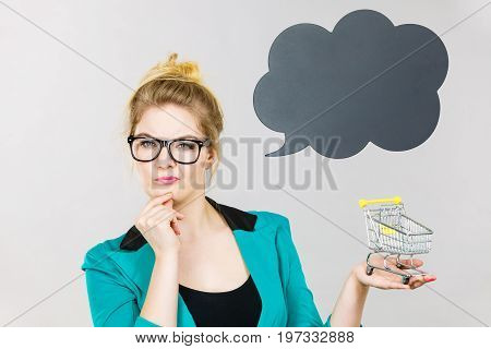 Thinking Business Woman Holding Small Tiny Shopping Cart