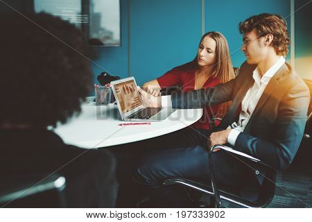 Beautiful businesswoman in red dress showing to her boss information graph on screen of laptop while they sitting on armchairs at oval table during business meeting or presentation in office settings