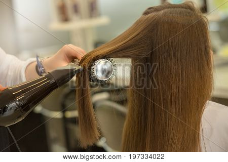Young female sitting in hair salon hairdo styling hair dry
