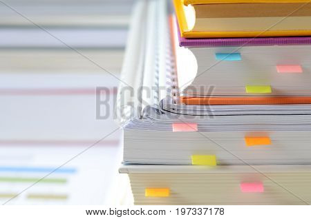 Pile of books and documents with paper notes on desk,high key tone,business concept.