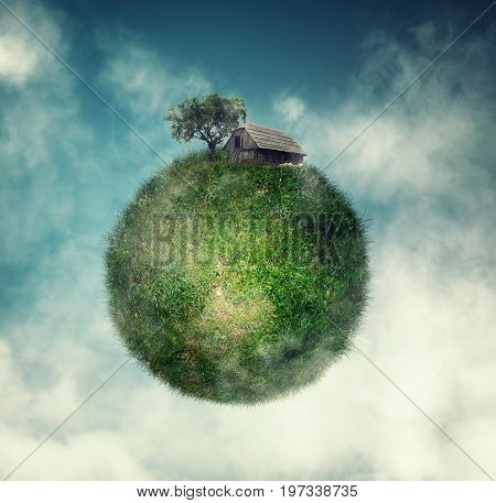 Globe of grass in the sky with a house and a tree on it.