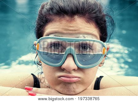 Young woman wearing swimming glasses half filled with water in the pool.