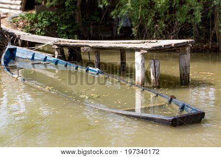 Drowned wooden boat near river pier in fresh water