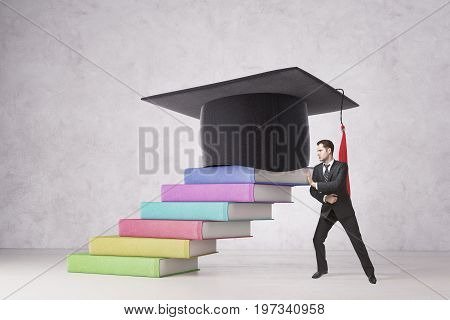 Businessman pushing abstract colorful book ladder with mortarboard on concrete background. Education and dedication concept. 3D Rendering