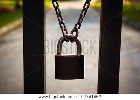 The lock hangs on the gate at the entrance to the closed territory.