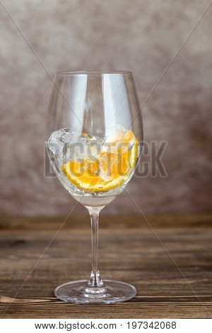 Glass with ice and orange on the wooden background