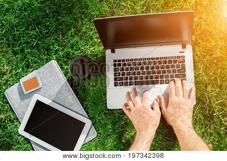 Close-up shot of handsome man's hands touching laptop computer's screen. Businessman using a laptop computer and sitting on the ground. Sun flare