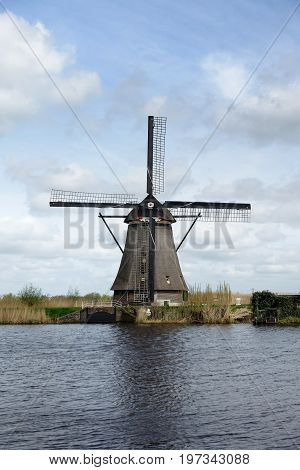 Dutch Windmill In The Afternoon Build And Standing Next To Polder Water In Kinderdijk South Holland