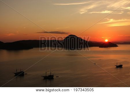 Orange Sunrise View From Padar Island Part Of Komodo National Park With Three Little Silhouette Boat