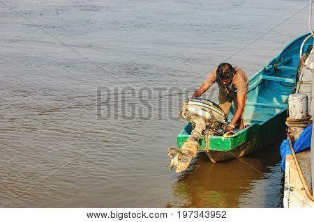 Goa, India - November 13, 2012: Lifestyle in Chorao island, Goa, India. Old boat for transportation to the Salim Ali Bird Sanctuary and its boatman starts the motor.