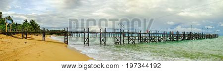 Koh Samui, Thailand - December 25, 2015: Old wooden pier stretching out to sea and foamy waves on the Maenam Beach. Koh Samui information sign at entrance to pier. People are resting on the beach