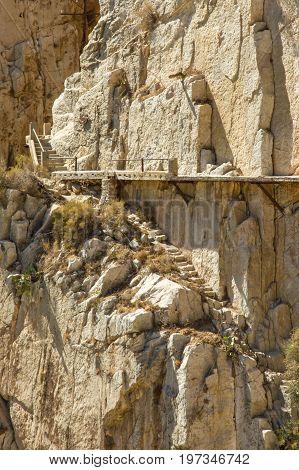 Yellow stone wall with rusty clamps, El Camino del Rey, Malaga, Spain