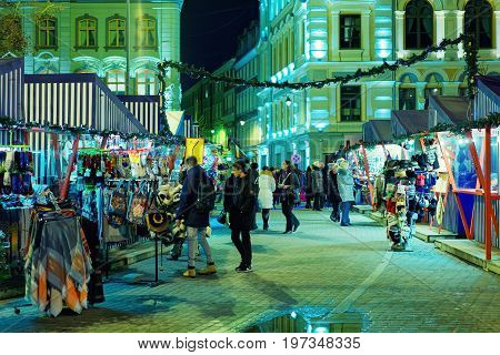 People At Christmas Market In Night Riga
