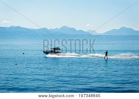 Motorboat With People Aboard And Man Wakesurfing At Lake Geneva
