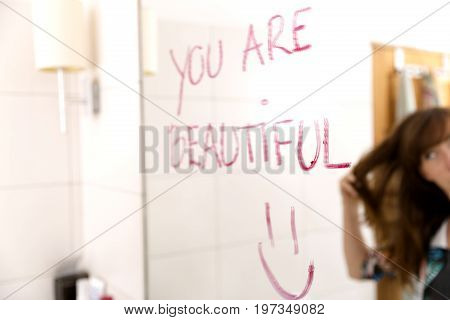 Women encouraging herself by writing words you are beautiful on mirror with lipstick