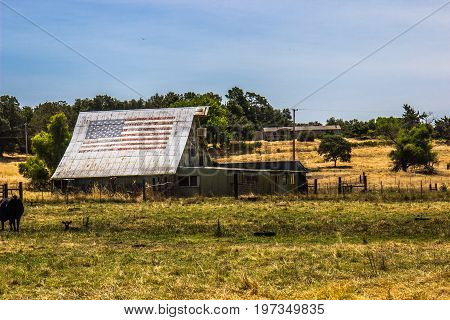 Old Barn On Ranch With Faded American Flag On Tin Roof