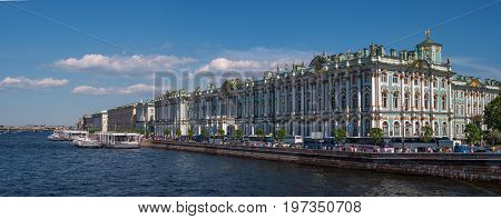 Hermitage palace on the bank of Neva river. On the waterfront there are many tour buses. The waterfront is moored excursion boats. Saint Petersburg, Russia.