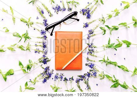 Weekly planner with pencil and glasses in frame with violet field flowers on the white background. Flat lay top view