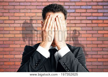 Businessman with angel and demon shadows on red brick wall background. True personality concept