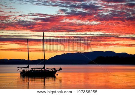 Silhouetted sailboat at sunset on the west coast of British Columbia, Canada