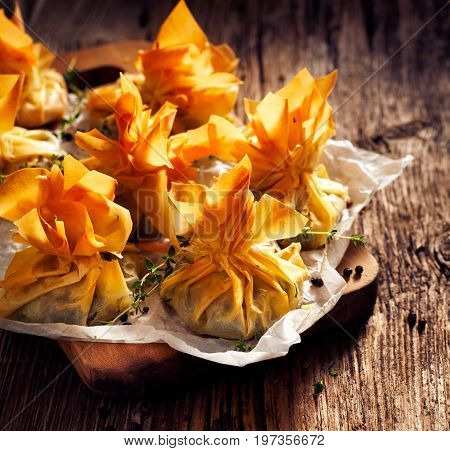 Spinach and Feta phyllo purses on a wooden rustic table, delicious vegetarian appetizers