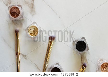 Neutral shades of loose mineral eyeshadows with small gold brushes. White marble copy space.