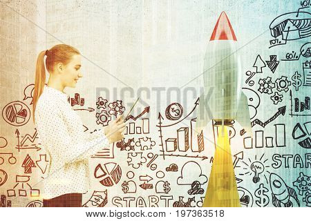 Side view of a blonde businesswoman with a laptop standing near a concrete wall with a rocket and start up icons. Mock up toned image double exposure
