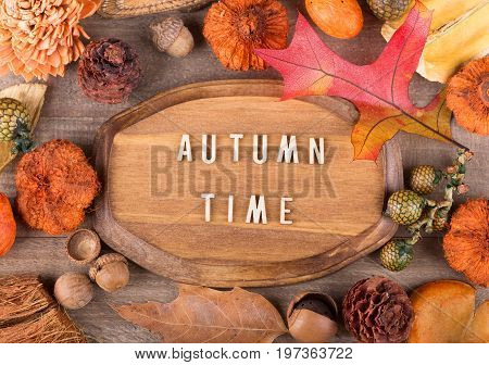 Wood plaque with autumn time text surrounded with colorful fall objects
