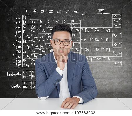 Portrait of a serious Asian man wearing a suit and glasses and sitting at a table near a blackboard with a periodic table on it.