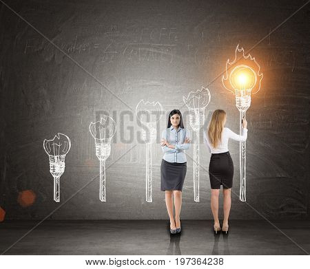 Portrait of two beautiful and smart business partners standing near a blackboard. One is drawing a light bulb torch. The second is thinking. Toned image