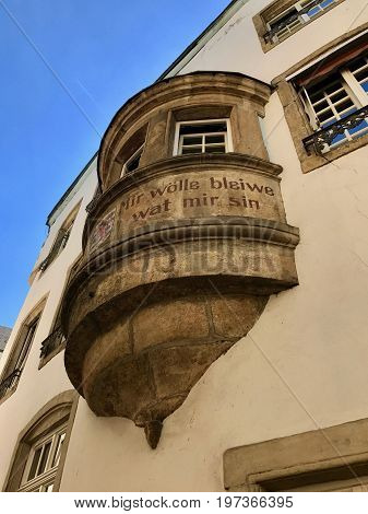The sign on the Luxembourg building states 'We shall never change'.