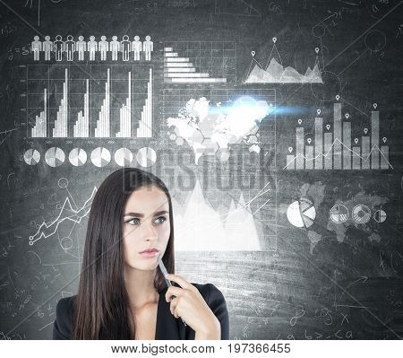 Portrait of a pensive businesswoman with a pen standing near a blackboard with graphs and a world map. Toned image.