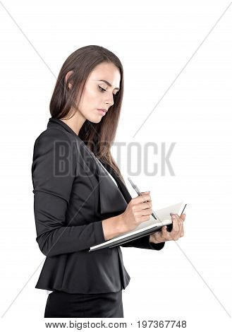 Isolated portrait of a beautiful young businesswoman wearing a black suit and holding a planner and a pen taking notes.