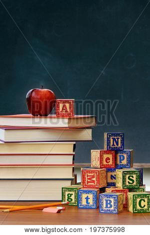 Stack of books and school bell on desk with chalkboard