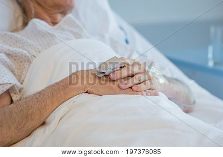 Closeup of hands of senior patient lying on hospital bed. Hand of old man with oxygen saturated probe in hospital room. Detail of wrinkled hands of elderly patient.