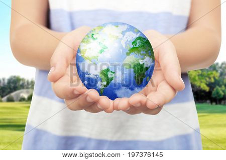 Little child holding globe in hands and landscape on background. Concept of aid
