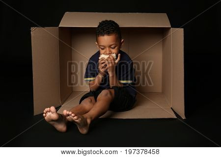 Cute little boy living in box on dark background. Poverty concept