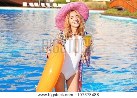 Beautiful young woman with swimming tube and glass of cocktail standing near pool