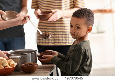Cute little boy waiting for food. Poverty concept
