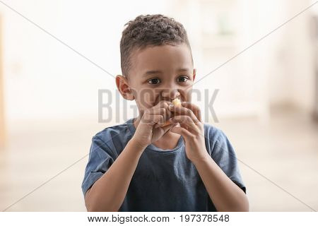 Cute little boy eating piece of bread on blurred background. Poverty concept