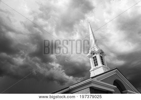 Black and White Church Steeple Tower Below Ominous Stormy Thunderstorm Clouds.