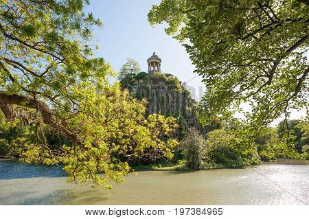 Temple de la Sibylle in the middle of a lake with trees in the foreground - Parc des Buttes Chaumont - Paris