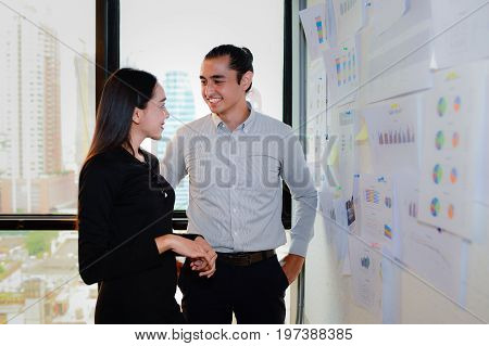 smile of business man and business woman stand and talk about business at the office