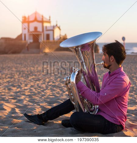Young musician playing the trumpet on the sea coast. Tuba instrument. In the background is the Chapel Senhor da Pedra at Miramar Beach, Atlantic ocean, Porto, Portugal.