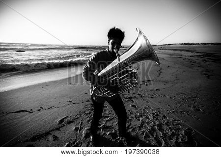 Musician playing the Tuba on the sea coast. High-contrast black-and-white photograph.