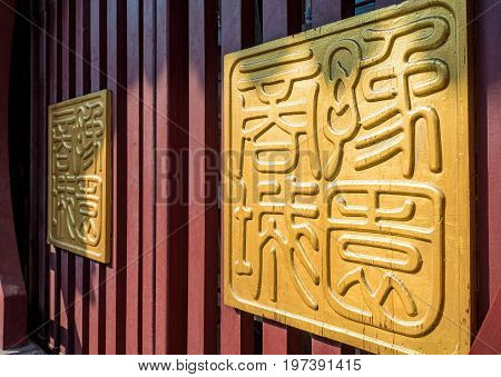 Shanghai, China - Nov 6, 2016: Fangbang Middle Road - Two huge golden Chinese traditional seals (with old-style Chinese characters) on wooden gates.