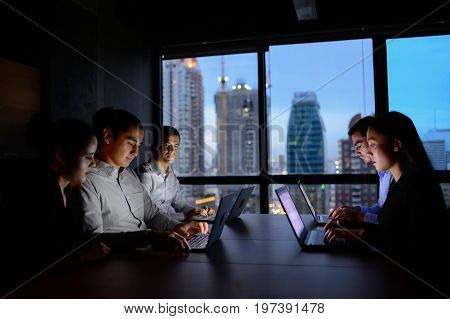 business man and business woman working with computer overtime at night and low light