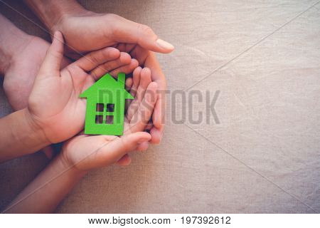 Adult and child hands holding green paper house eco house concept
